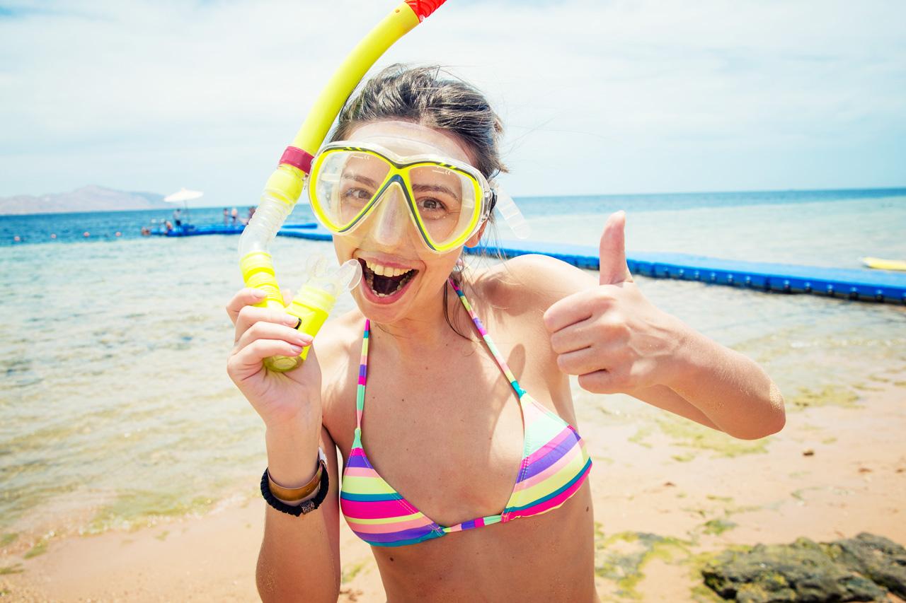 jente på stranden med snorklemaske
